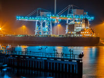 Ship unloading coal in a harbor. Nautical ship on a wharf during dusk is unloaded with modern cranes under colorful lighting Royalty Free Stock Photo