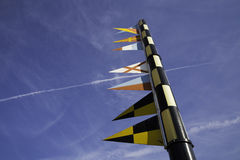 Nautical signal flags on a flagpole against blue sky Stock Photos