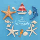 Nautical and summer holidays concept with sea life style objects, seashells and starfish over blue wooden background. Nautical and summer holidays concept with Royalty Free Stock Photo