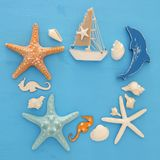 Nautical and summer holidays concept with sea life style objects, seashells and starfish over blue wooden background. Nautical and summer holidays concept with Royalty Free Stock Photography
