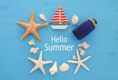 Nautical and summer holidays concept with sea life style objects, seashells and starfish over blue wooden background. Nautical and summer holidays concept with Royalty Free Stock Images