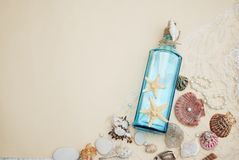 Nautical Theme Backdrop, Decorative Bottle with Shells, Starfish on Neutral Ivory Background. Place for text. Selective focus. Nautical Theme Backdrop Royalty Free Stock Images