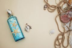 Nautical Theme Backdrop, Decorative Bottle with Shells, Starfish on Neutral Ivory Background. Place for text. Selective focus. Royalty Free Stock Image