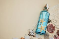 Nautical Theme Backdrop, Decorative Bottle with Shells, Starfish on Neutral Ivory Background. Place for text. Selective focus. stock photography