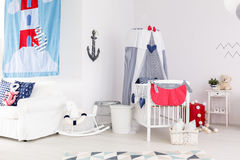 Nautical theme nursery with toys. Like rocking horse, bed and cradle stock photo