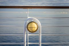 Nautical white outdoor deck lamp with brass metal fitting aboard cruise ship. stock images