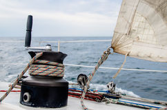 Nautical Winch and the used Sail. A nautical winch used to trim an old and used sail during a sailing day Royalty Free Stock Photos