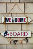 Nautical Wooden Welcome Aboard Sign. Hand painted wooden welcome aboard sign hanging on a rustic shingled building Stock Image