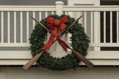 Nautical wreath with old worn oars and sparkly red bow mounted on wooden porch - closeup stock image