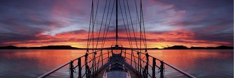 Nautisk karmosinröd soluppgång med fartyg- och vattenreflexioner Arkivfoto