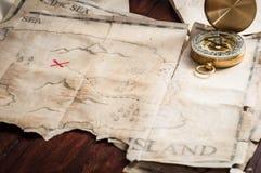 Nautisk kompass på skattöversikt av den abstrakta ön på trätabellen Royaltyfri Fotografi