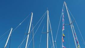 Nautiska flaggor mot blå himmel, färgrika signalflaggor på en segelbåt i solsken stock video
