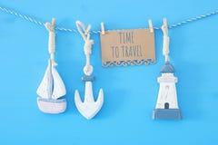 nautiskt begrepp med havslivsstilgarneringar: segla fartyget och ankaret som hänger på en rad över blå träbakgrund Royaltyfri Fotografi