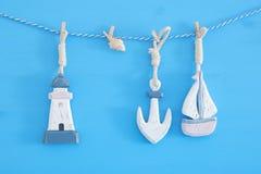 nautiskt begrepp med havslivsstilgarneringar: segla fartyget och ankaret som hänger på en rad över blå träbakgrund Royaltyfria Bilder