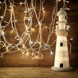 nautiskt livsstilbegrepp gammal tappningfyr på trätabellen och varma guld- girlandljus tappning filtrerad bild arkivbild
