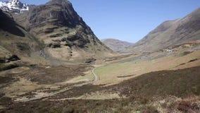 Nauwe vallei van Schotland het UK van de Glencoevallei de beroemde Schotse met bergen in Schotse Hooglanden in de lentepan stock footage