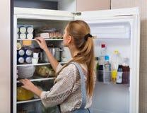 Nauwkeurig en positief meisje die zich dichtbij koelkast bevinden royalty-vrije stock fotografie