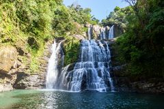 Nauyaca Falls, Costa Rica. Nauyaca waterfalls with a deep swimming hole and large rocks in the south pacific of Costa Rica, a popular hiking destination royalty free stock photo