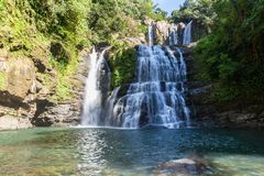 Nauyaca Falls, Costa Rica. Nauyaca waterfalls with a deep swimming hole and large rocks in the south pacific of Costa Rica, a popular hiking destination stock photography