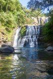 Nauyaca Falls, Costa Rica. Nauyaca waterfalls with a deep swimming hole and large rocks in the south pacific of Costa Rica, a popular hiking destination stock photo