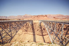 Navajo Bridge. Is a pair of steel spandrel arch bridges that cross the Colorado River near Lee`s Ferry in northern Arizona. The newer bridge of the pair carries royalty free stock image