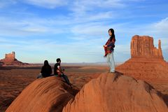 Navajo woman standing and two Navajo musicians sitting playing music on rocks stock images