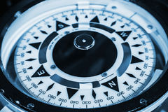 Naval compass. Blue toned macro photo Stock Photos