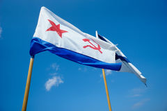 Naval flag of USSR and Russia on blue sky background. Two flags on background of blue sky. Naval flag of the USSR - red star, hammer and sickle. And Naval flag Royalty Free Stock Image