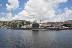 Naval submarine moored in large river Stock Photo