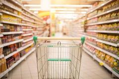 Navata laterale del supermercato con il carrello rosso vuoto immagine stock libera da diritti