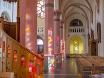 Nave-aisle of the 19th-century Parish Church of St. Lawrence, St. Laurentius with beautiful colorful sunlight window reflections o stock images