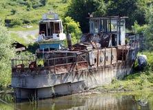 Nave arrugginita rotta che sta sulla sponda del fiume Fotografia Stock Libera da Diritti