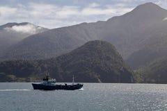 Nave da carico che attraversa i fiordi patagonian. Fotografie Stock