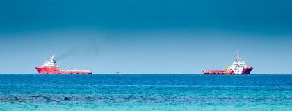 Nave da carico di due rossi sul mare Immagini Stock