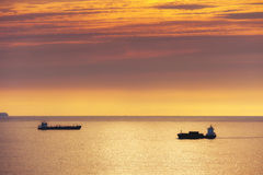 Nave da carico ed autocisterna del petrolio al tramonto Immagine Stock
