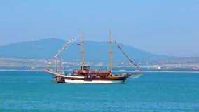 Nave de madera enorme hermosa en derivas del estilo del pirata en la superficie azul del mar contra costa y las montañas de mar almacen de video