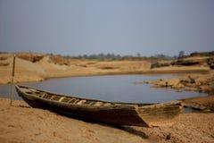 Nave de madera vieja dañada en la tierra seca Fotografía de archivo