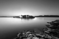 Nave de Sunked que se inclina en el lado cerca de una costa rocosa imagenes de archivo