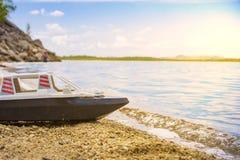 Nave del giocattolo sul primo piano sabbioso della riva dell'oceano su fondo vago con effetto del bokeh immagini stock