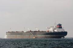 Nave del petrolero gigante del petróleo en el mar con el barco experimental. Foto de archivo