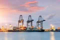 Nave del trasporto del carico del contenitore con il ponte funzionante della gru in cantiere navale al crepuscolo per alba logist Fotografia Stock
