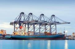 Nave del trasporto del carico del contenitore con il ponte funzionante della gru in cantiere navale al crepuscolo per importazion Fotografie Stock