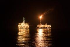 Nave dell'autocisterna di FPSO vicino all'impianto offshore alla notte Petrolio marino e industria del gas immagini stock libere da diritti