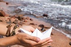 Nave di carta in mani Immagine Stock