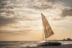 Nave di navigazione sulla spiaggia durante il tramonto Fotografie Stock