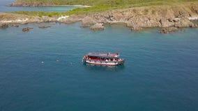Nave di navigazione di vista aerea in scogliera blu della montagna e del mare sulla riva Gente turistica che nuota in chiare acqu stock footage