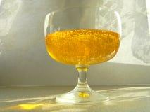 Nave di vetro con miele I raggi del ` s del sole splendono sul vetro Fotografia Stock