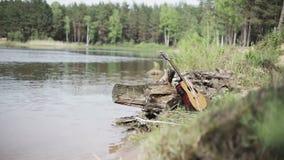 nave Die vergessene Gitarre auf der Bank des Sees stock video footage