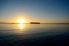 Nave en el horizonte en la salida del sol Foto de archivo