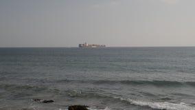 Nave grande, de alta mar del buque de petróleo con los envases que pertenecen a Hapag Lloyd según lo visto de la costa portuguesa almacen de metraje de vídeo